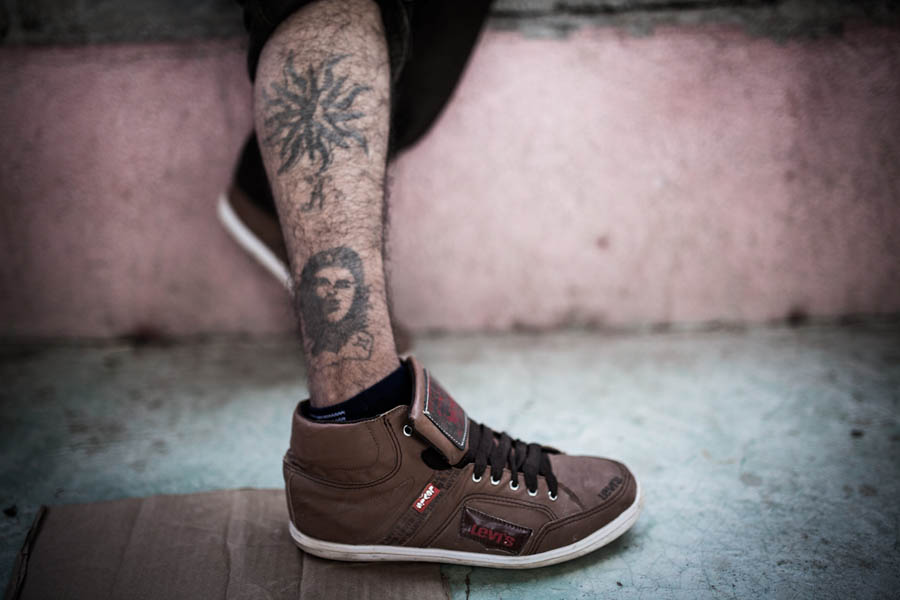 A young migrant from Guatemala shows his tattoo of Che Guevara.