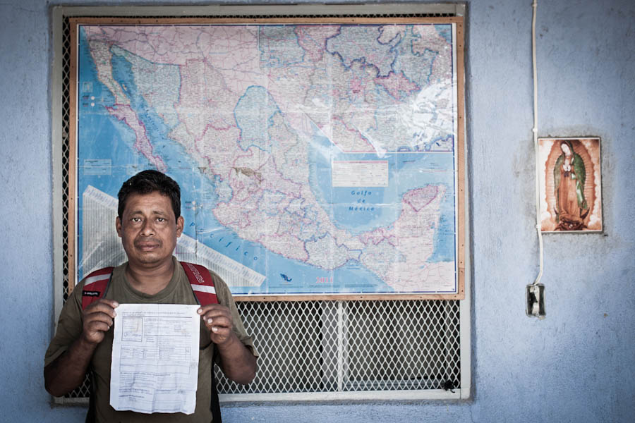Erik is a hard worker whose entire family is in the United States. In this photo he shows his deportation papers with a map outlining the train route north behind him.